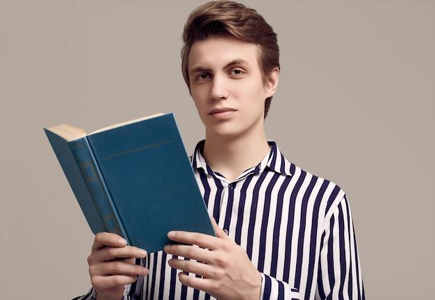 Jonge knappe man in gestreepte shirt lezen van een boek op grijze achtergrond