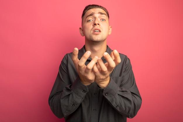 Jonge knappe man in grijs overhemd armen stak als bedelen met hoop expressie staande over roze muur