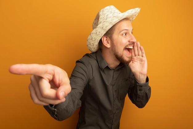 Jonge knappe man in grijs overhemd en zomerhoed schreeuwen of iemand bellen met de hand in de buurt van de mond en met wijsvinger naar iets wijzen