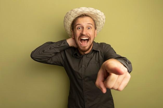 Jonge knappe man in grijs overhemd en zomerhoed verbaasd en met wijsvinger op camera wijzend