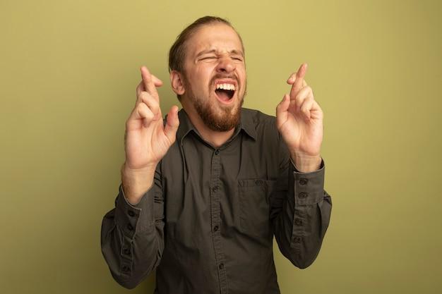Jonge knappe man in grijs overhemd wenselijke wens maken met gesloten ogen vingers kruisen met hoop expressie