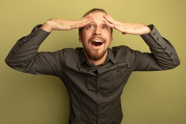 Jonge knappe man in grijs shirt blij en opgewonden met handen op zijn hoofd opzoeken