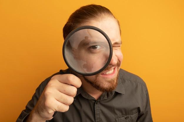 Jonge knappe man in grijs shirt door vergrootglas