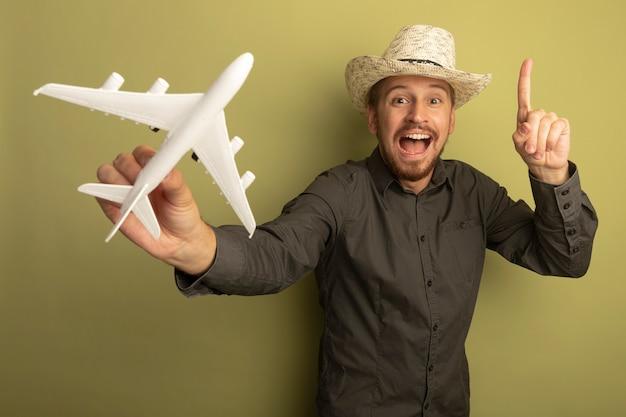 Jonge knappe man in grijs shirt en zomerhoed speelgoed vliegtuig gelukkig en positief glimlachend vrolijk tonen duimen omhoog