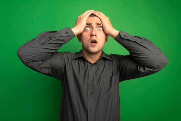 Jonge knappe man in grijs shirt kijken naar voorkant gek verbaasd en verrast met handen op zijn hoofd staande over groene muur