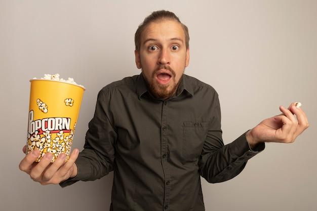 Jonge knappe man in grijs shirt met emmer met popcorn op zoek verward schouders ophalen