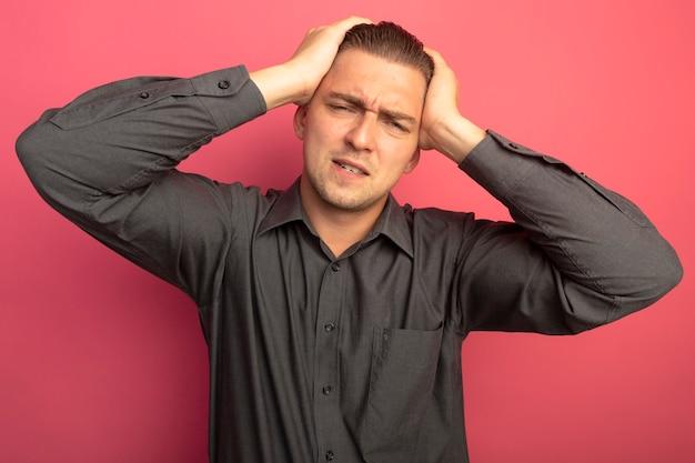 Jonge knappe man in grijs shirt met handen op zijn hoofd voor fout wordt verward en erg angstig