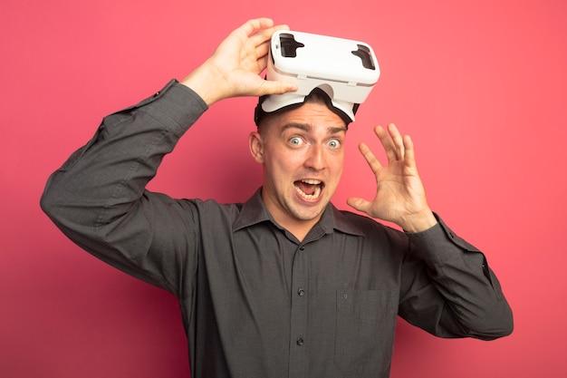 Jonge knappe man in grijs shirt met virtual reality-bril naar voorkant kijken opgewonden en blij met opgeheven hand staande over roze muur