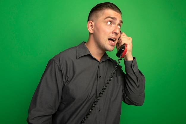 Jonge knappe man in grijs shirt praten over vintage telefoon opzij kijken verward staande over groene muur