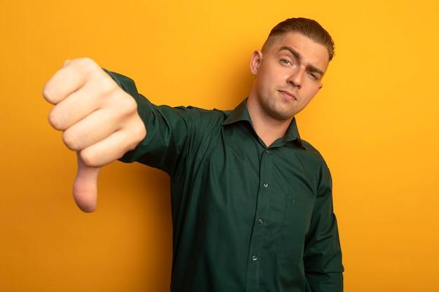 Jonge knappe man in groen shirt ontevreden weergegeven: afkeer
