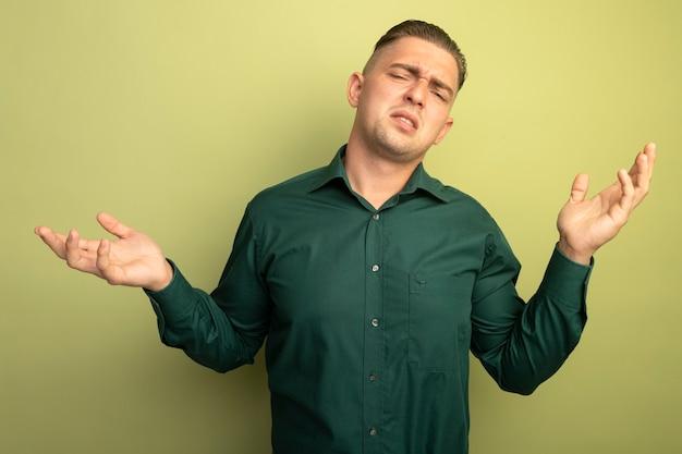 Jonge knappe man in groen shirt verward en ontevreden met armen zoals vragen