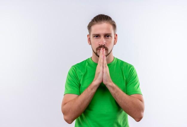Jonge knappe man in groen t-shirt hand in hand samen bidden met open ogen kijken camera met ernstige gezicht staande op witte achtergrond