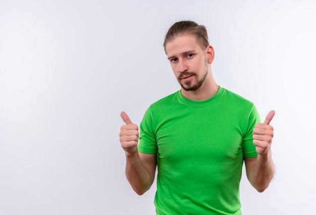 Jonge knappe man in groen t-shirt kijken camera glimlachen vriendelijk tonen duimen omhoog staan op witte achtergrond
