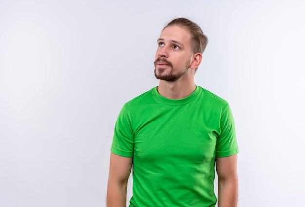 Jonge knappe man in groen t-shirt opzij kijken met peinzende uitdrukking op gezicht staande op witte achtergrond