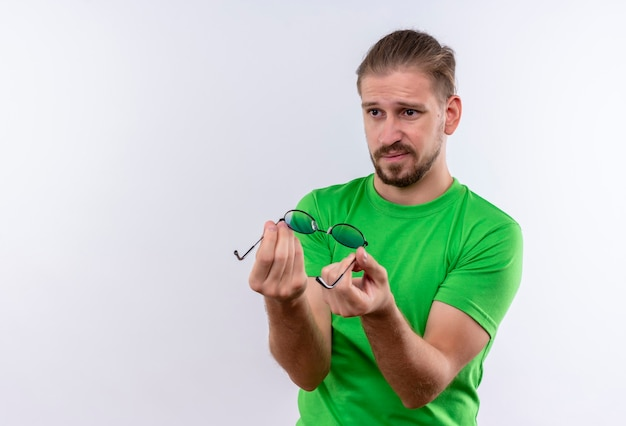 Jonge knappe man in groene t-shirt zonnebril in handen houden opzij kijken met sceptische uitdrukking op gezicht staande op witte achtergrond