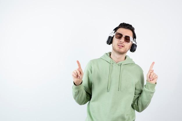 Jonge knappe man in koptelefoon luisteren naar muziek.