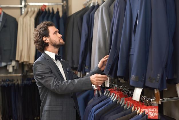 Jonge knappe man in kostuum op zoek naar jas in winkel.