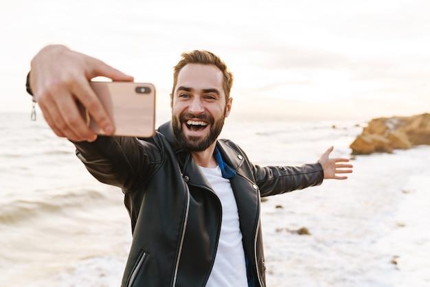 Jonge knappe man in leren jas selfie foto nemen op smartphone tijdens het wandelen langs de kust