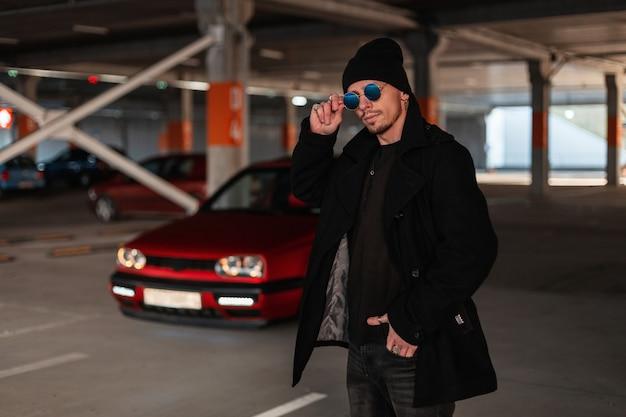Jonge knappe man in modieuze kleding met een zwarte jas en een hoed die zijn vintage zonnebril aanpast tegen de achtergrond van een rode auto op de parkeerplaats