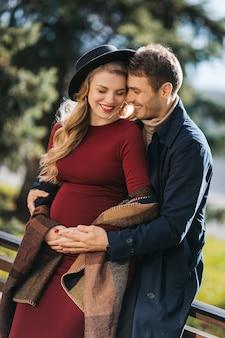 Jonge knappe man in regenjas knuffelt zijn zwangere vrouw in rode jurk en stijlvolle hoed in het park aan de...