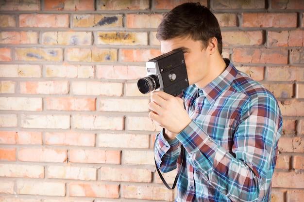 Jonge knappe man in shirt met lange mouwen nemen foto met behulp van vintage camera met bakstenen muur achtergrond.