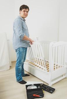Jonge knappe man in spijkerbroek en shirt die babybedje in elkaar zet