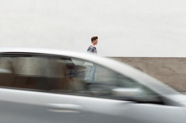 Jonge knappe man in stijlvolle blauwe denim kleding voor jongeren loopt op straat in de buurt van de weg. modieuze man met casual jeans loopt door de stad in de buurt van een bewegende auto