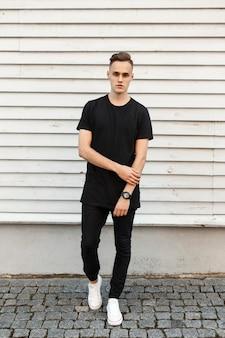 Jonge knappe man in witte sneakers poseren in de buurt van een lichte houten muur.