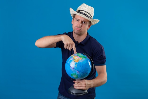 Jonge knappe man in zomer hoed bedrijf globe wijzend met vinger naar het met droevige uitdrukking op gezicht staande over blauwe achtergrond