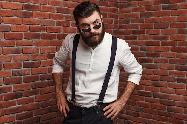 Jonge knappe man in zonnebril poseren op bakstenen muur.