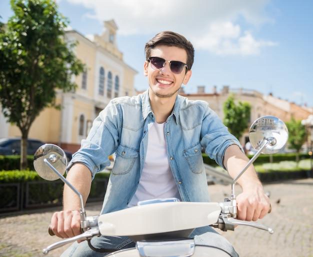 Jonge knappe man in zonnebril rijden scooter.