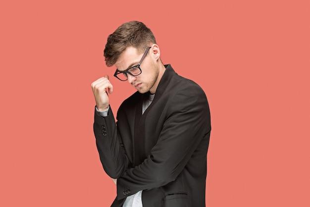 Jonge knappe man in zwart pak en bril geïsoleerd op rode muur