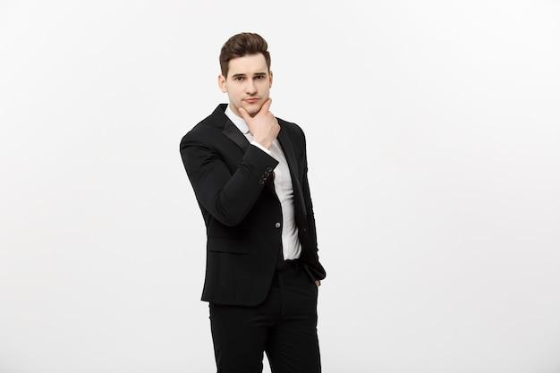 Jonge knappe man in zwart pak en bril kijkend naar kopie-ruimte denken of dromen geïsoleerd op witte achtergrond