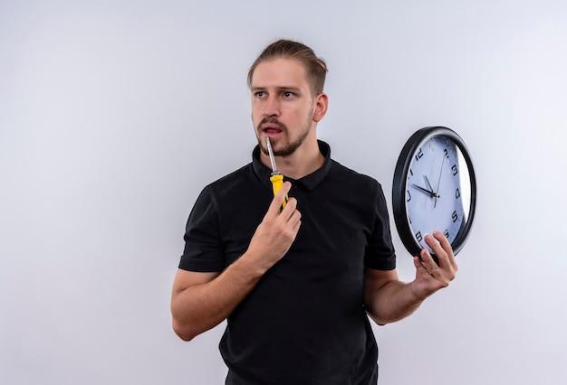 Jonge knappe man in zwart poloshirt met wandklok en schroevendraaier opzij kijken met peinzende uitdrukking op gezicht staande op witte achtergrond