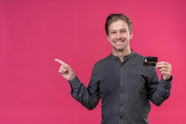 Jonge knappe man in zwart shirt met creditcard, wijzend met de vinger naar de zijkant