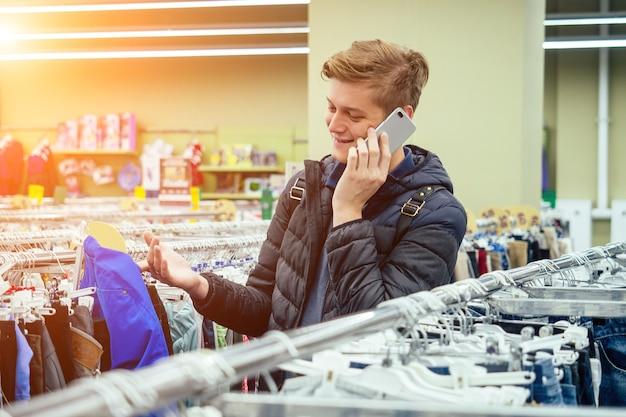 Jonge knappe man kiest kleding in het winkelcentrum en praat aan de telefoon