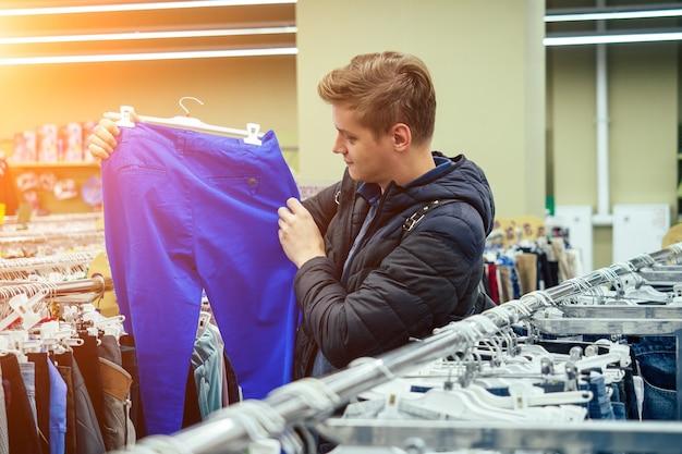 Jonge knappe man kiest kleding in het winkelcentrum