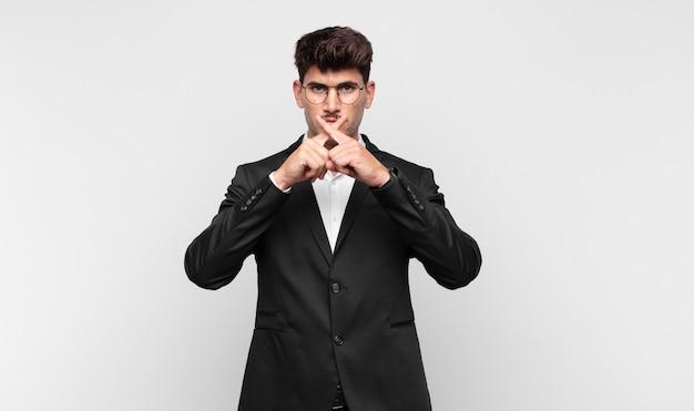 Jonge knappe man kijkt ernstig en ontevreden met beide vingers gekruist van voren in afwijzing, vragend om stilte