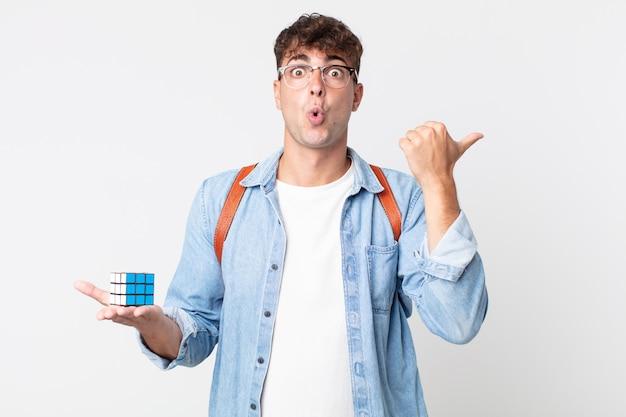 Jonge knappe man kijkt verbaasd in ongeloof. intelligentie spelconcept