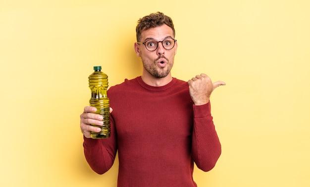 Jonge knappe man kijkt verbaasd in ongeloof. olijfolie concept