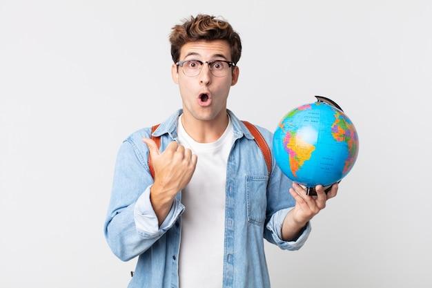 Jonge knappe man kijkt verbaasd in ongeloof. student met een wereldbolkaart