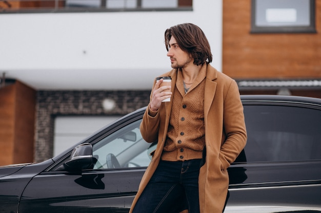 Jonge knappe man koffie buiten drinken in de winter