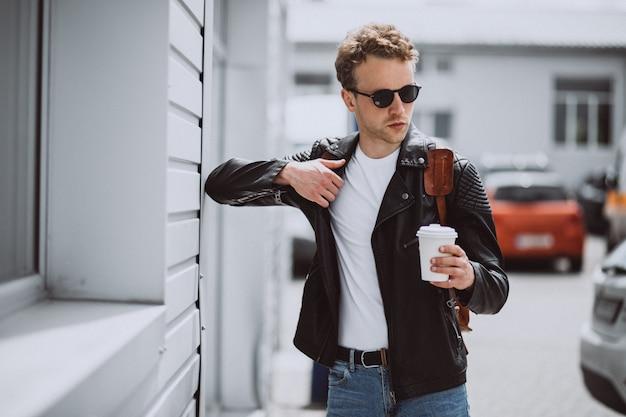 Jonge knappe man koffie drinken in de straat