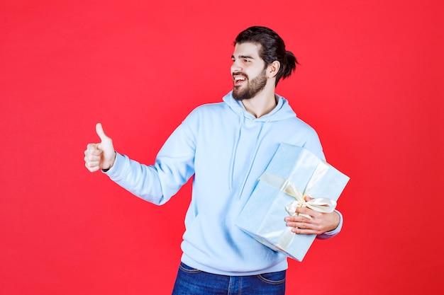 Jonge knappe man lacht en houdt zijn cadeau vast terwijl hij gebaart
