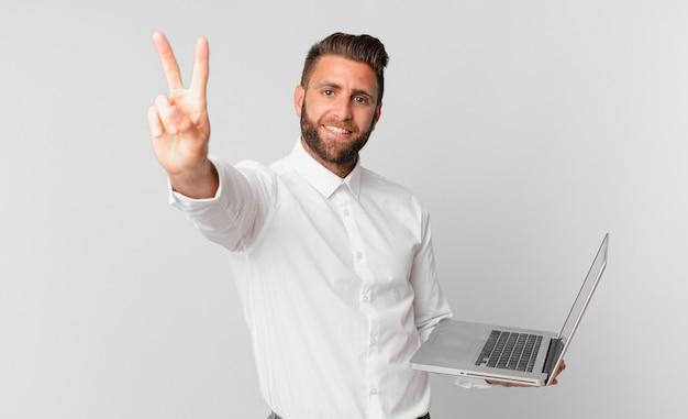 Jonge knappe man lacht en ziet er gelukkig uit, gebaart overwinning of vrede en houdt een laptop vast