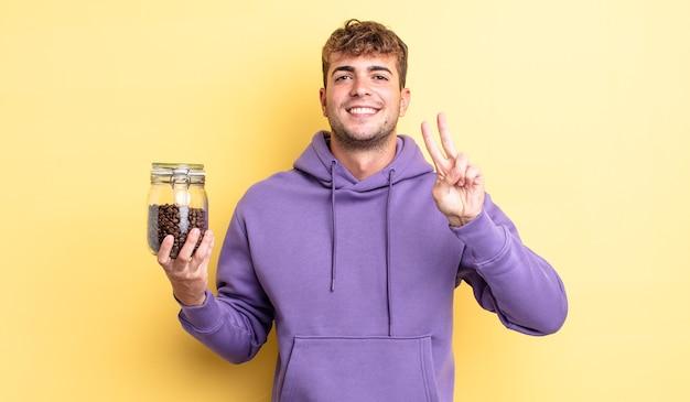 Jonge knappe man lacht en ziet er gelukkig uit, gebarend overwinning of vrede. koffiebonen concept