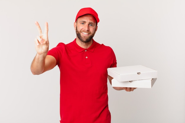 Jonge knappe man lacht en ziet er gelukkig uit, gebarend overwinning of vrede. pizza bezorgconcept