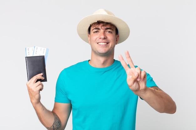 Jonge knappe man lacht en ziet er gelukkig uit, gebarend overwinning of vrede. reiziger met zijn paspoort