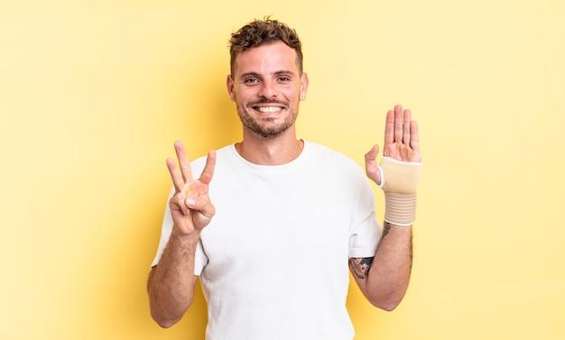Jonge knappe man lacht en ziet er vriendelijk uit, met nummer drie. handverband concept