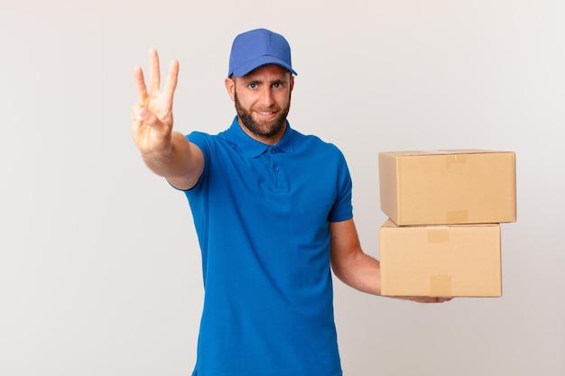 Jonge knappe man lacht en ziet er vriendelijk uit, met nummer drie. pakket leveren concept